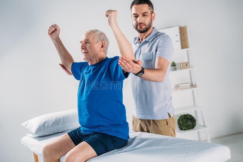 portrait du physiothérapeute focalisé faisant le massage à l'homme supérieur photographie stock