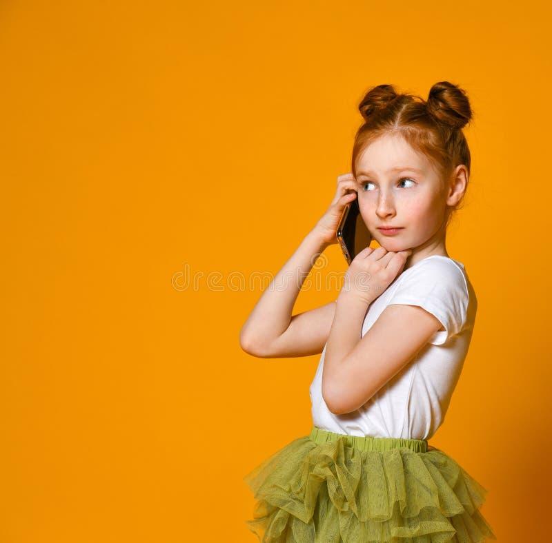 Portrait du positif de petite fille que parlant aux t?l?phones portables photographie stock libre de droits