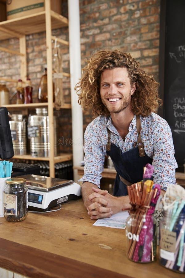 Portrait du propriétaire masculin de l'épicerie libre en plastique viable derrière le bureau de ventes photographie stock