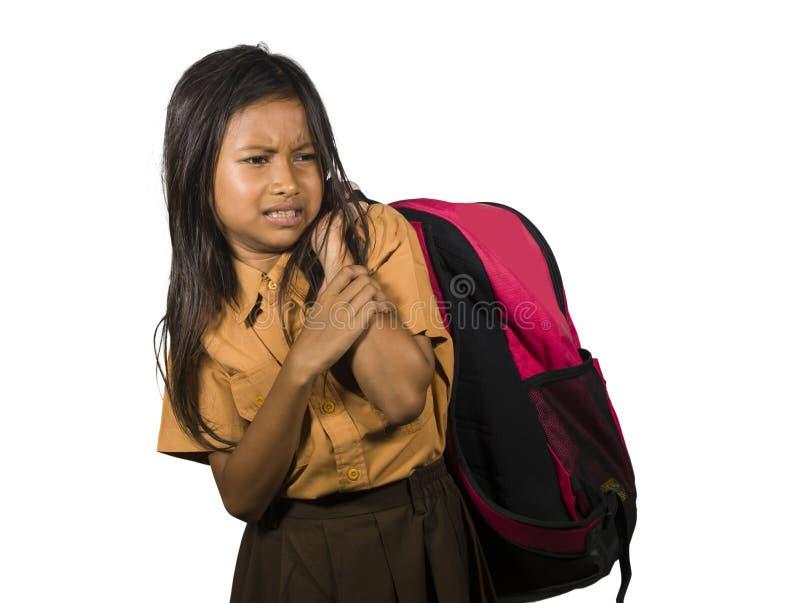 Portrait du renversement et du bel enfant féminin portant le sac d'école lourd complètement des manuels et de la lutte de devoirs photographie stock libre de droits