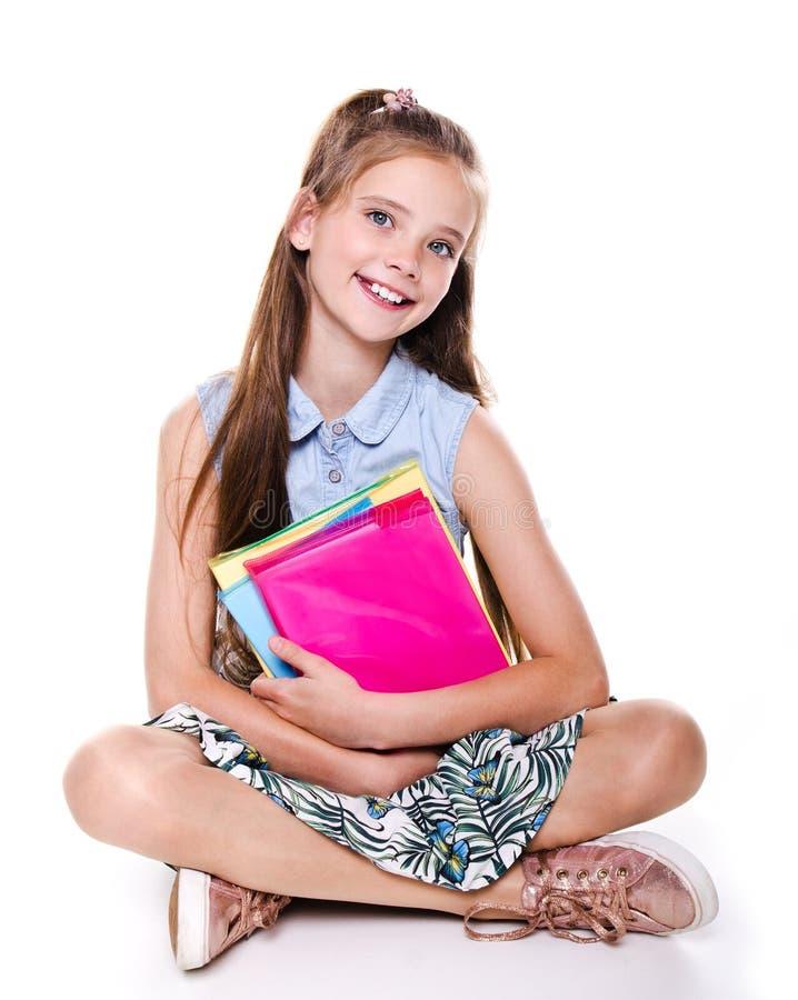 Portrait du sourire mignon heureux petit adolescent d'enfant de fille d'?cole s'asseyant sur un plancher et jugeant les livres d' photographie stock libre de droits