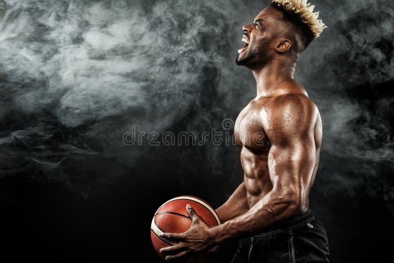 Portrait du sportif afro-américain, joueur de basket avec une boule au-dessus de fond noir Jeune homme convenable dans les vêteme photographie stock libre de droits