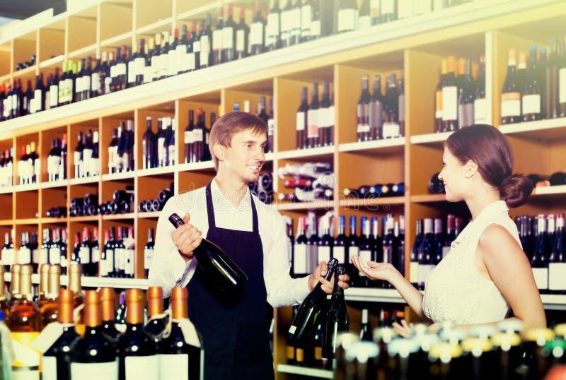Portrait du vendeur masculin montrant la bouteille de vin à la coutume femelle image stock
