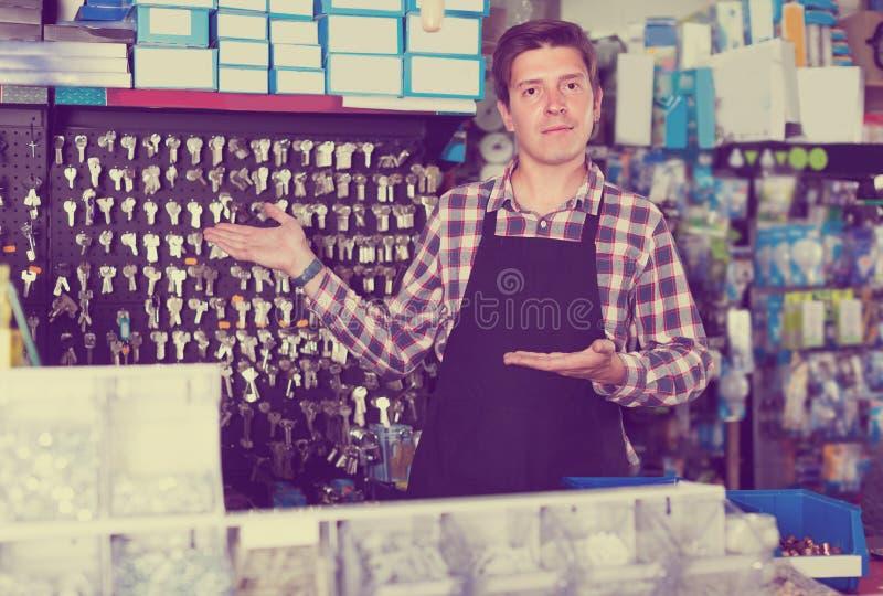 Portrait du vendeur masculin qui est vendant et fabriquant des clés photographie stock libre de droits