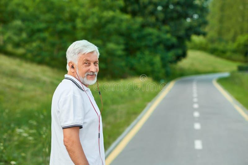 Portrait du vieil homme de sourire se tenant sur le champ de courses du ` s de ville regardant l'appareil-photo photo stock