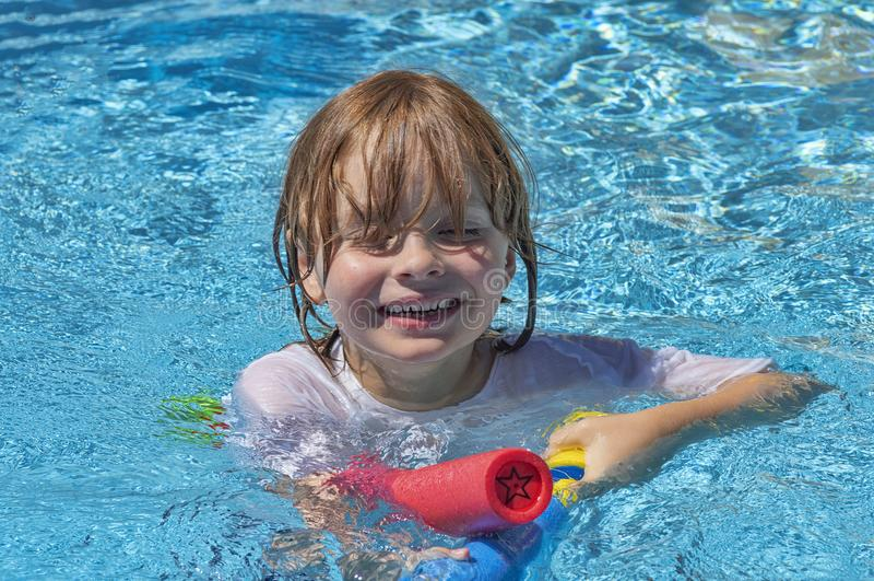 Portrait du visage et du coffre d'un garçon 7 se situant dans la piscine et jouant avec son arme à feu d'eau image libre de droits