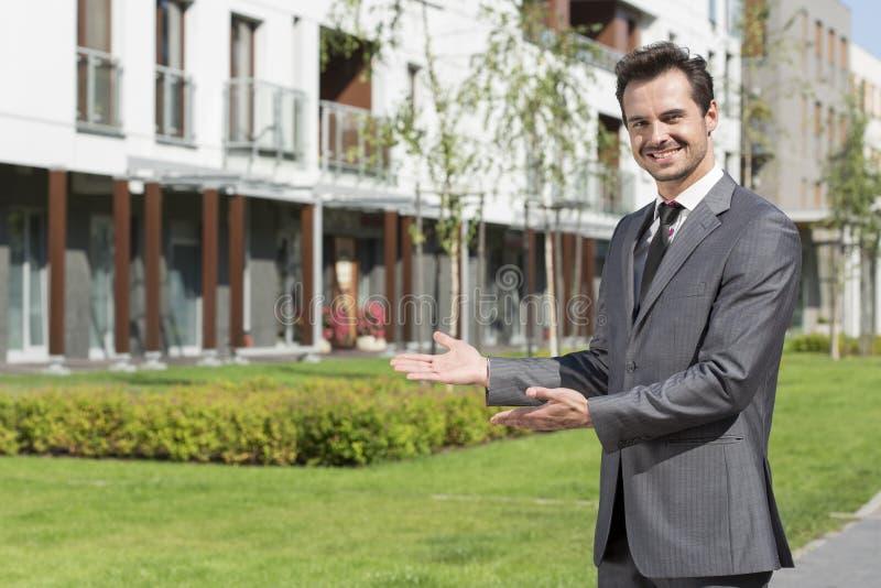 Portrait du vrai agent immobilier heureux présentant l'immeuble de bureaux photo stock