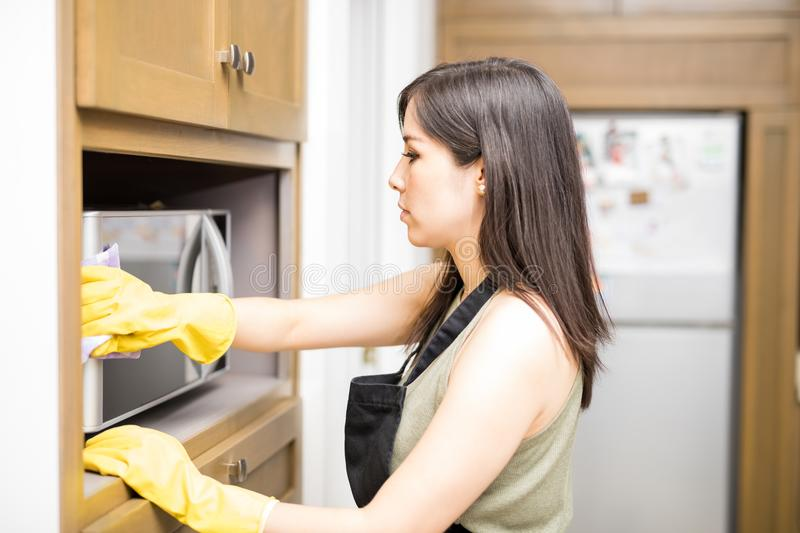 Serious young woman cleaning oven stock photography