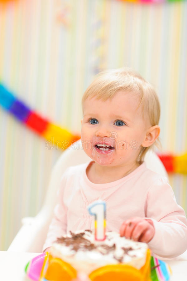 Portrait of eat smeared baby with birthday cake. Portrait of eat smeared baby girl with birthday cake stock images