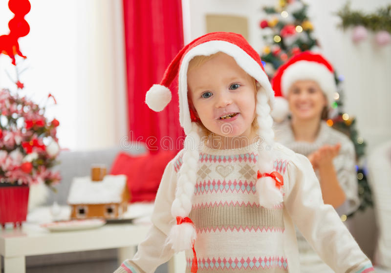 Portrait of eat smeared baby in Christmas hats royalty free stock images