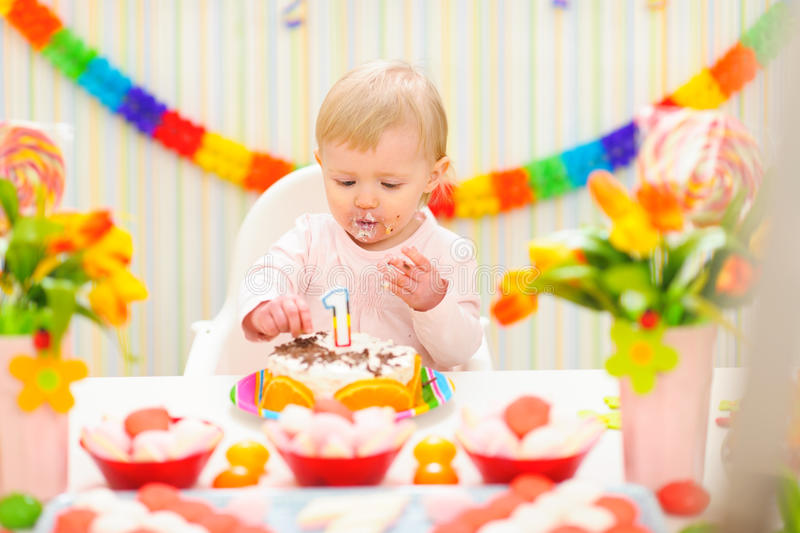 Portrait of eat smeared baby eating birthday cake. Portrait of eat smeared baby girl eating birthday cake royalty free stock photography