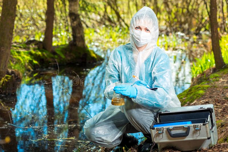 Portrait of an ecologist in protective clothing while working, taking water samples from a forest river. For analysis stock images
