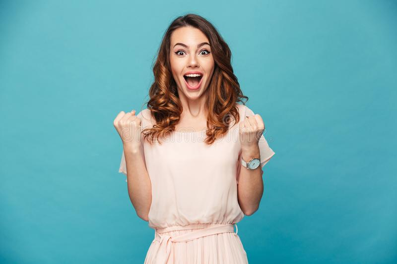 Portrait of ecstatic woman 20s wearing dress screaming and clenching fist like rejoicing victory or triumph, isolated over blue b. Portrait of ecstatic woman 20s stock image