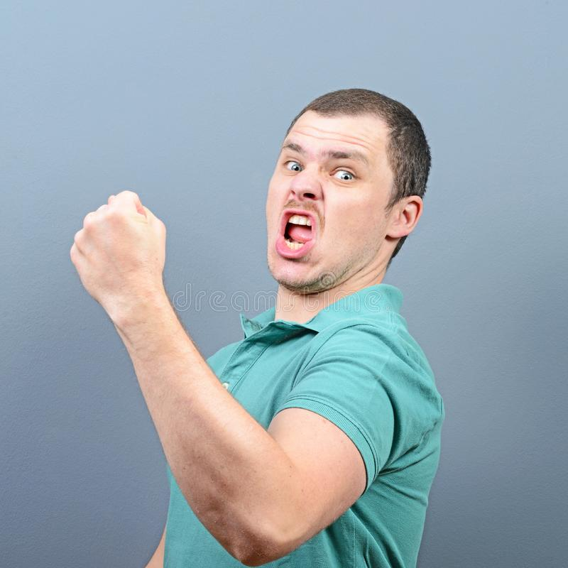 Portrait of ecstatic young man celebrating victory or win against gray background stock image
