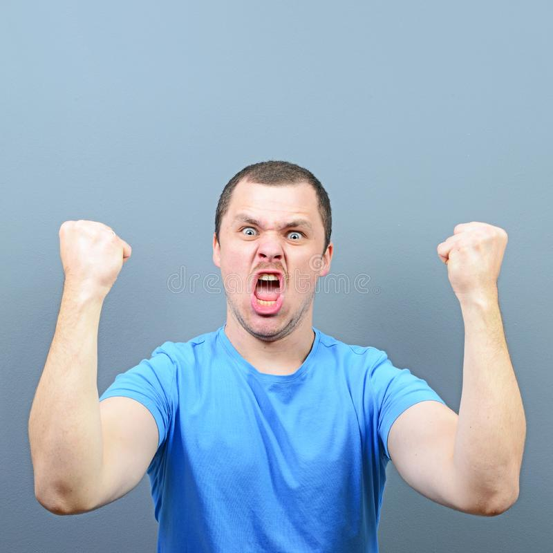 Portrait of ecstatic young man celebrating victory or win against gray background royalty free stock photo
