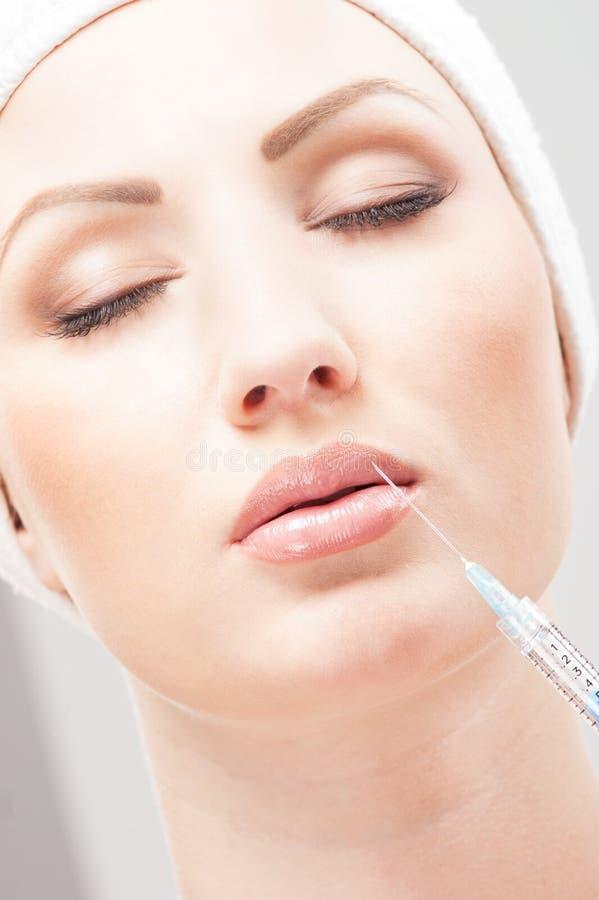 Portrait einer Frau, die botox in ihre Lippe einspritzt lizenzfreie stockfotos
