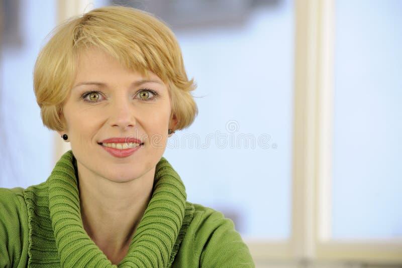 Portrait einer Frau, die eine grüne Strickjacke trägt stockbild