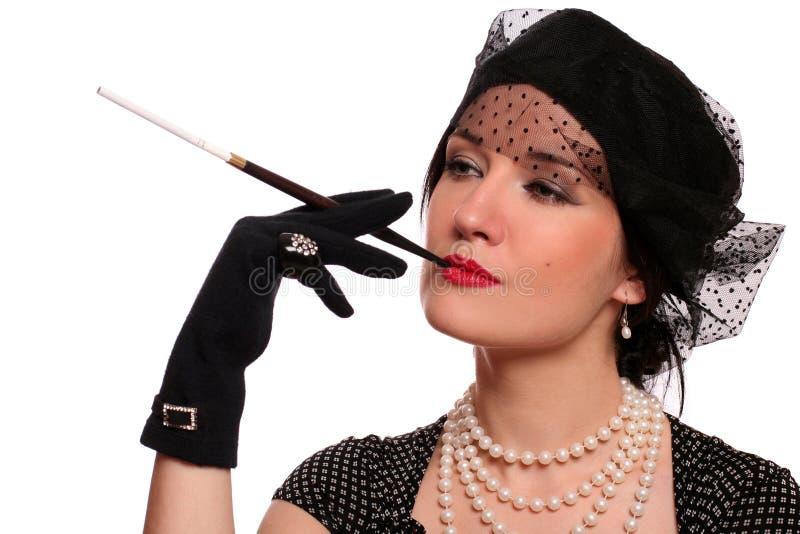 Portrait einer Frau mit einer Zigarettenspitze. stockbilder