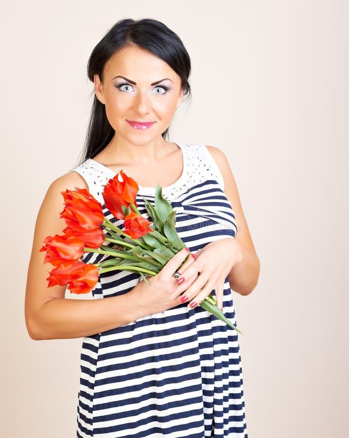 Portrait einer Frau mit roten Blumen, Studioschuß lizenzfreies stockbild