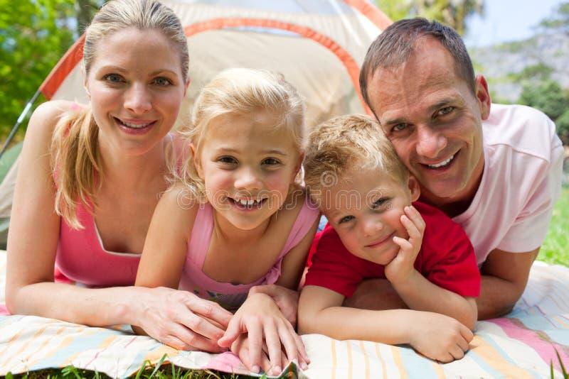 Portrait einer glücklichen Familie, die auf dem Gras liegt lizenzfreie stockfotos