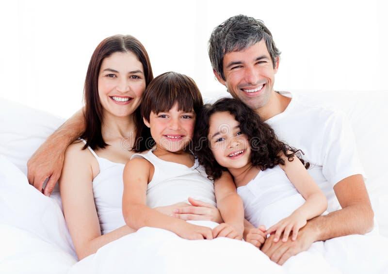 Portrait einer glücklichen Familie, die auf einem Bett sitzt lizenzfreie stockfotos