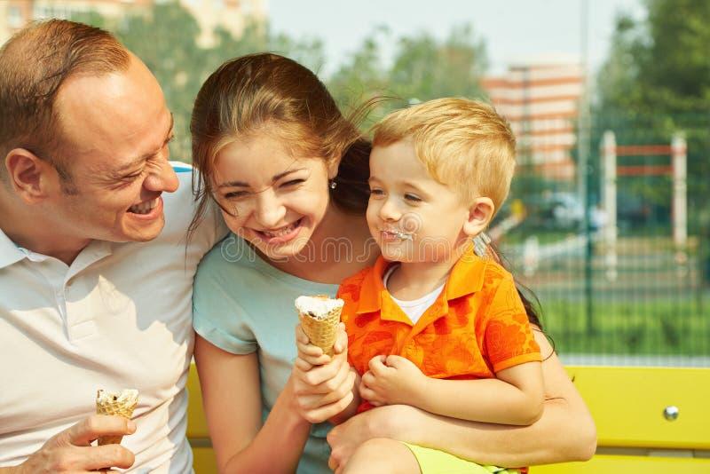 Portrait einer glücklichen Familie Mutter, Vati und Kind, die Eiscreme essen lizenzfreie stockfotos