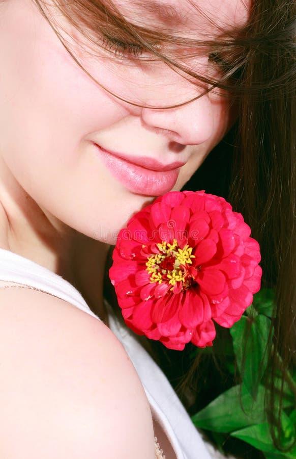 Portrait einer glücklichen jungen Frau mit einer Blume stockbild