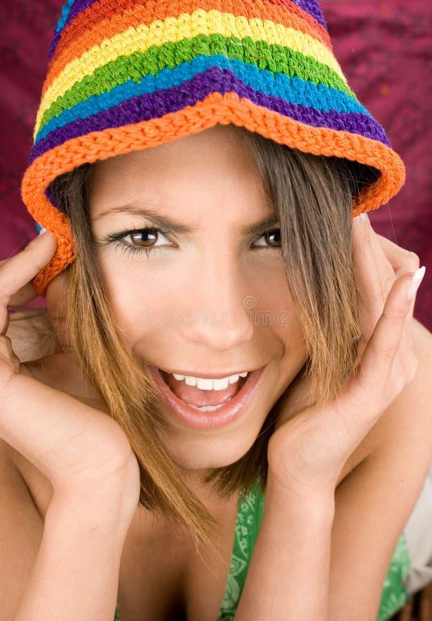 Portrait einer glücklichen jungen Frau mit Farbenhut stockbild