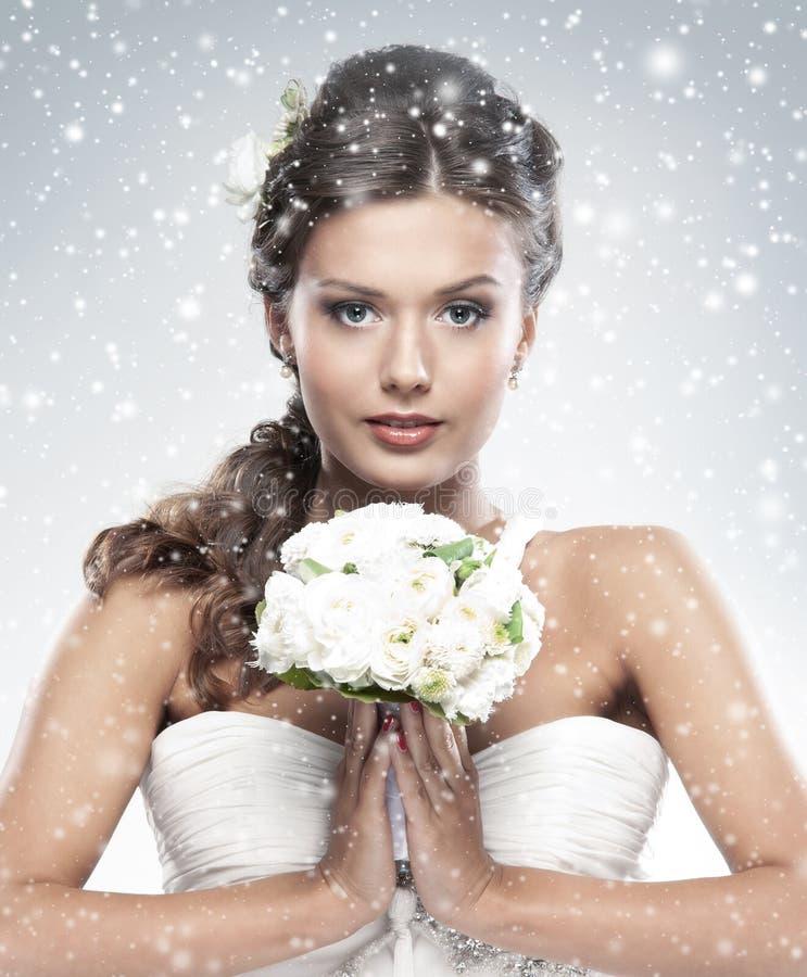 Portrait einer jungen Braut, die weiße Blumen anhält stockfotografie