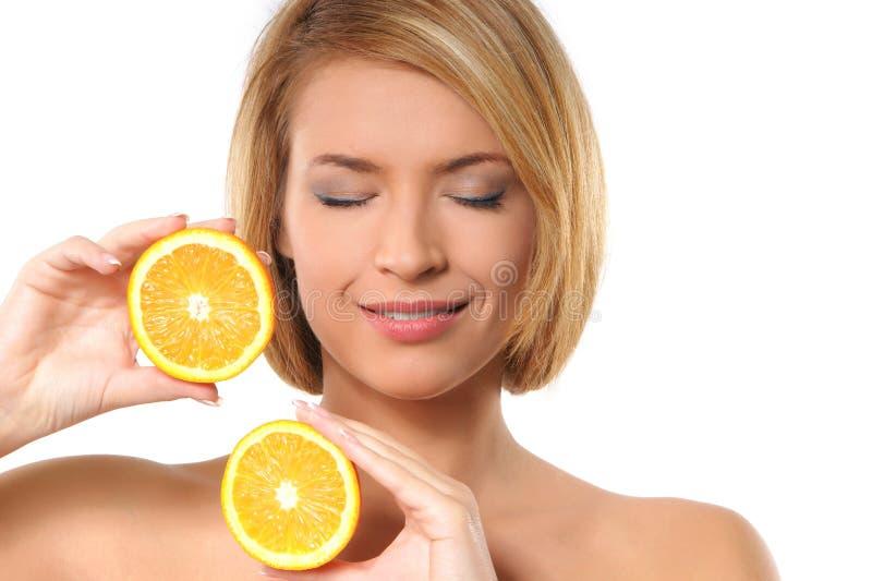 Portrait einer jungen Frau, die zwei Orangen anhält lizenzfreie stockbilder
