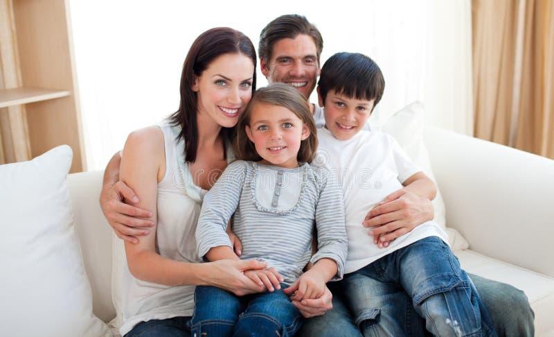 Portrait einer lächelnden Familie, die auf dem Sofa sitzt stockbild