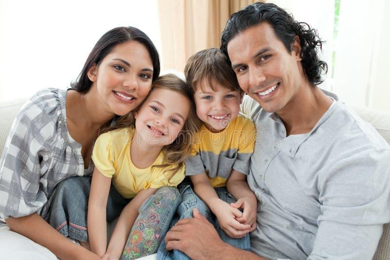 Portrait einer lächelnden Familie, die auf Sofa sitzt lizenzfreies stockfoto