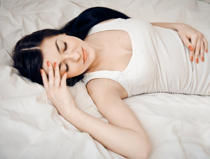 Portrait einer netten jungen Frau, die auf dem Bett schläft stockfotos