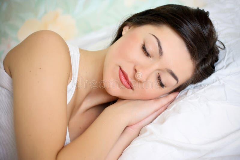 Portrait einer netten jungen Frau, die auf dem Bett schläft lizenzfreie stockfotos