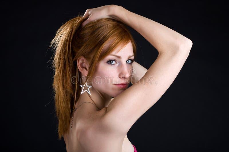 Portrait einer Redheadfrau auf dunklem Hintergrund stockfotografie