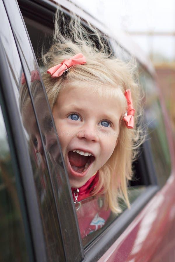 Portrait eines überraschten Mädchens in einem Auto lizenzfreie stockfotos
