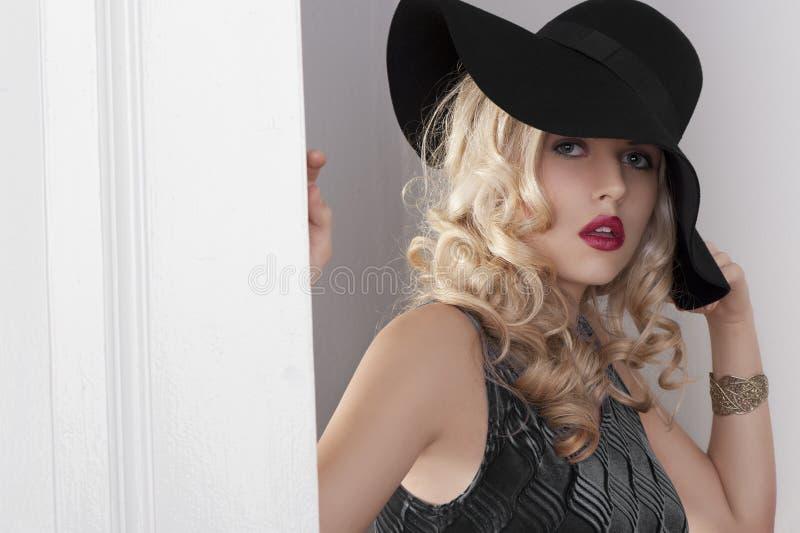 Portrait eines Art und Weisemädchens mit schwarzem Hut lizenzfreie stockfotos
