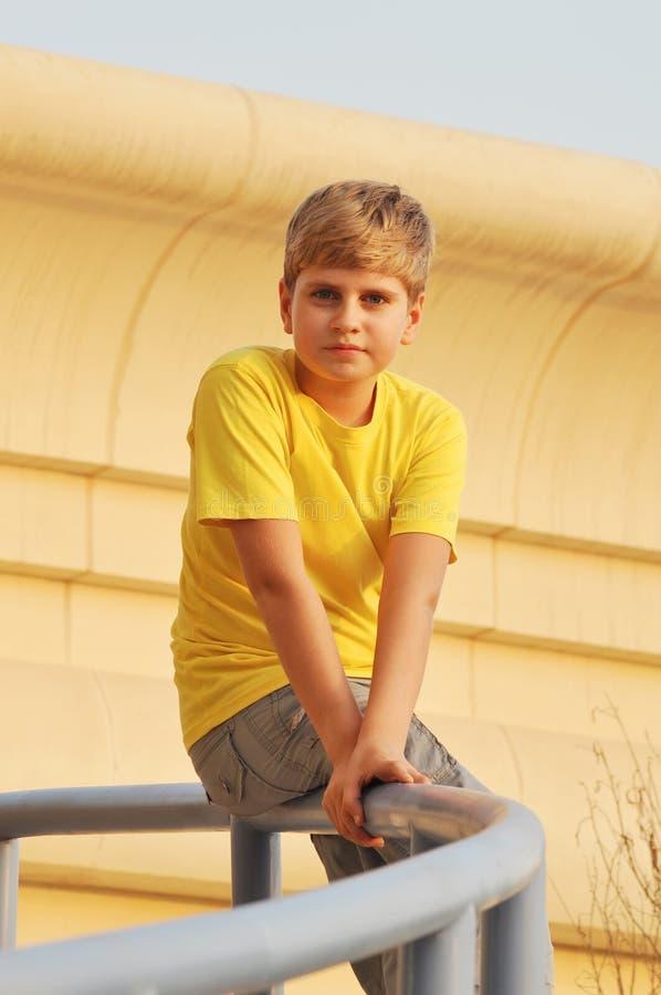 Portrait eines blonden Jungen, der auf Geländerdocke sitzt lizenzfreies stockbild