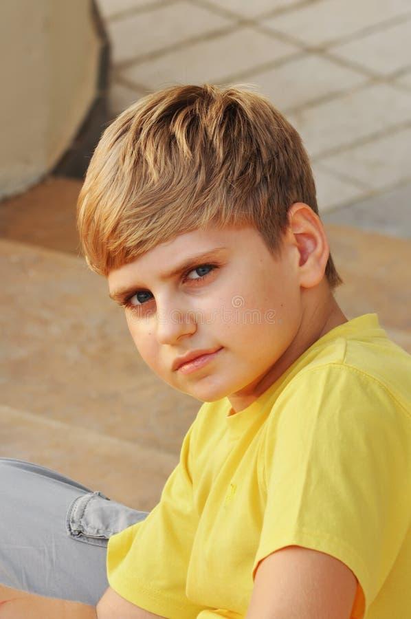 Portrait eines blonden Jungen, der auf Treppen sitzt stockfotos