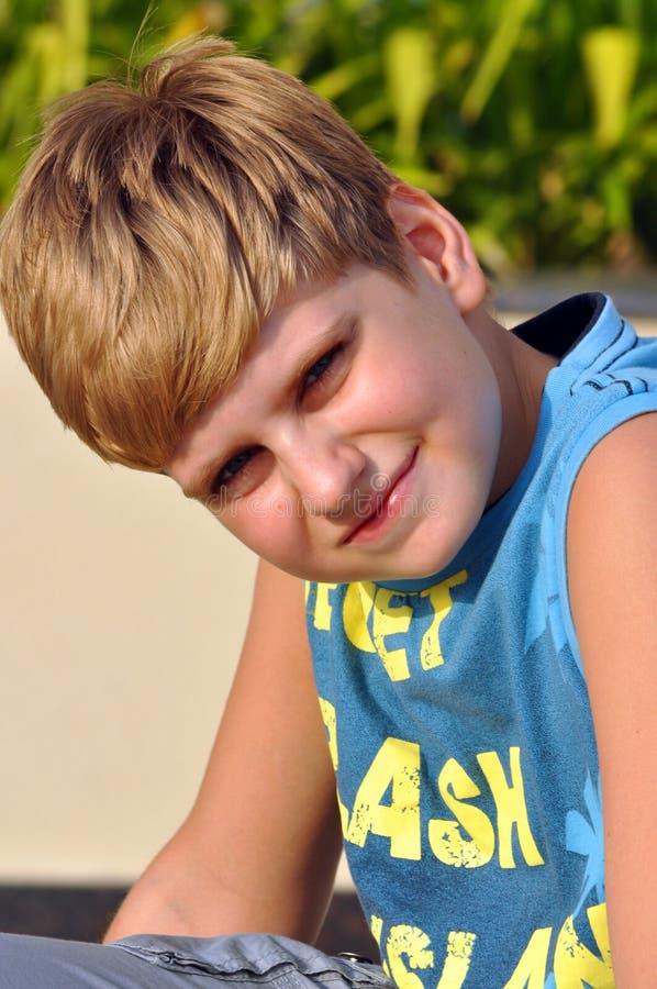 Portrait eines blonden Jungen, der Kamera betrachtet stockbilder