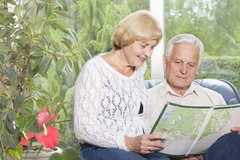 Portrait eines glücklichen alten Paares, das Karte analysiert lizenzfreie stockfotografie