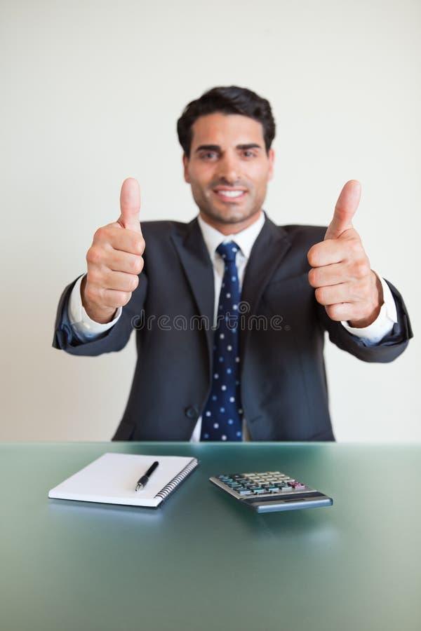 Portrait eines jungen Buchhalters mit den Daumen oben lizenzfreie stockbilder