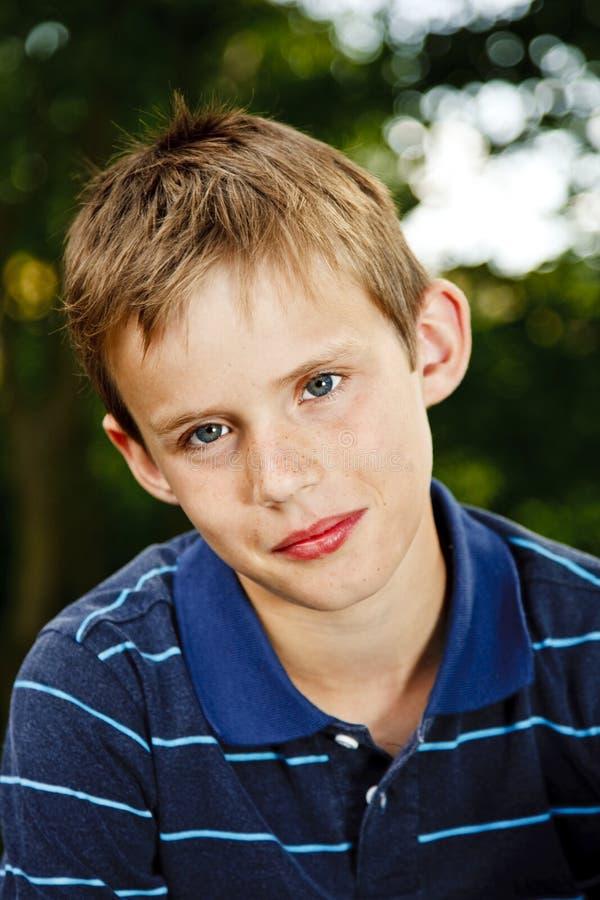 Portrait eines jungen Jungen, der im Garten sitzt stockbild
