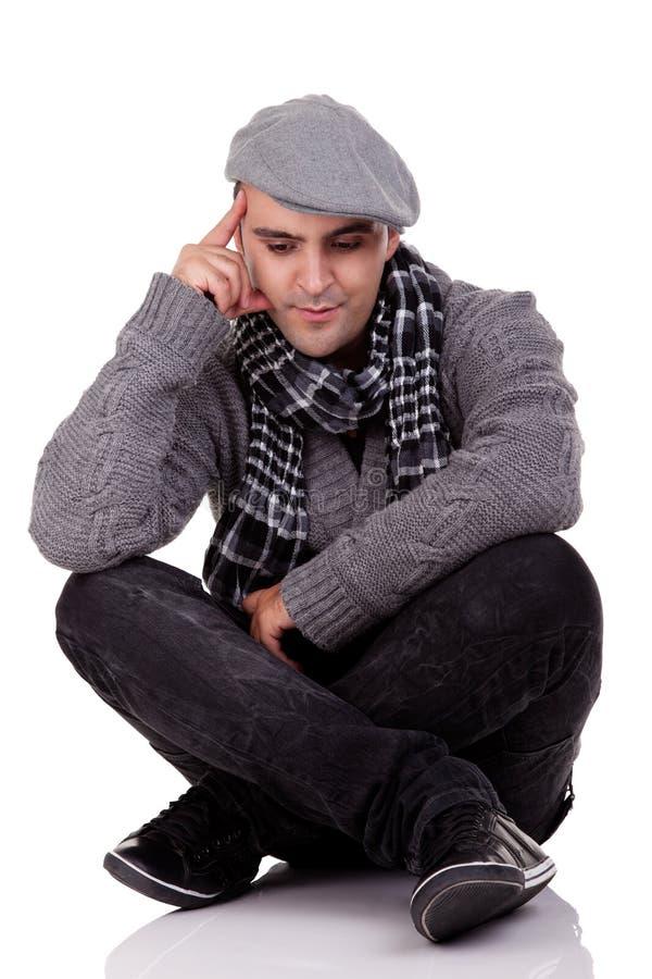Portrait eines jungen Mannes, der auf dem Fußboden sitzt stockbild