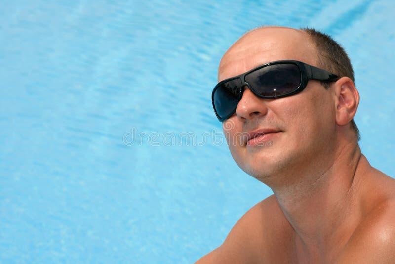 Portrait eines jungen Mannes nahe dem Swimmingpool lizenzfreies stockfoto
