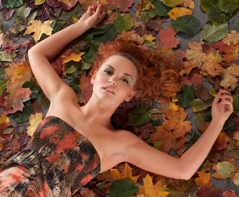 Portrait eines jungen Redheadmädchens auf gefallenen Blättern stockfoto