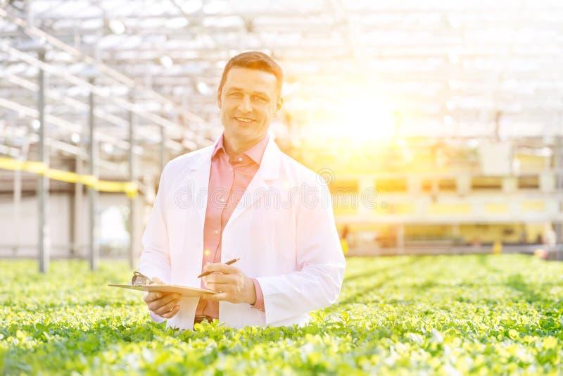 Portrait eines lächelnden Wissenschaftlers mit Zwischenwand inmitten von Kräutern im Gewächshaus stockfotografie