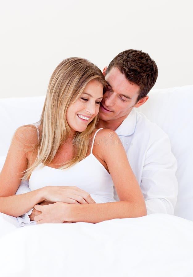 Portrait eines liebevollen Paares, das auf Bett sitzt stockfotos