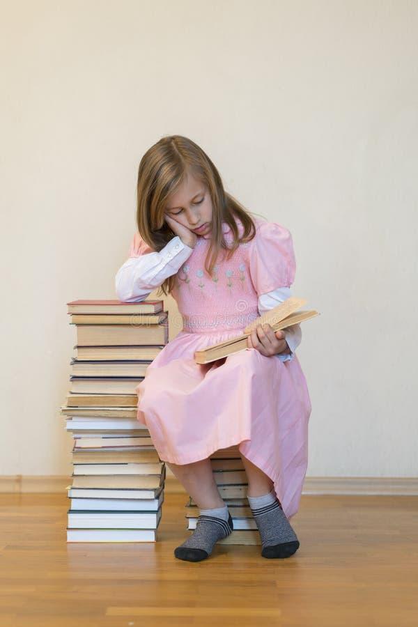 Portrait eines M?dchenjugendlich-Lesebuches Bildung und Schulkonzept Das Kind liest Ein kleines nettes Mädchen in einem rosa Klei stockfotos