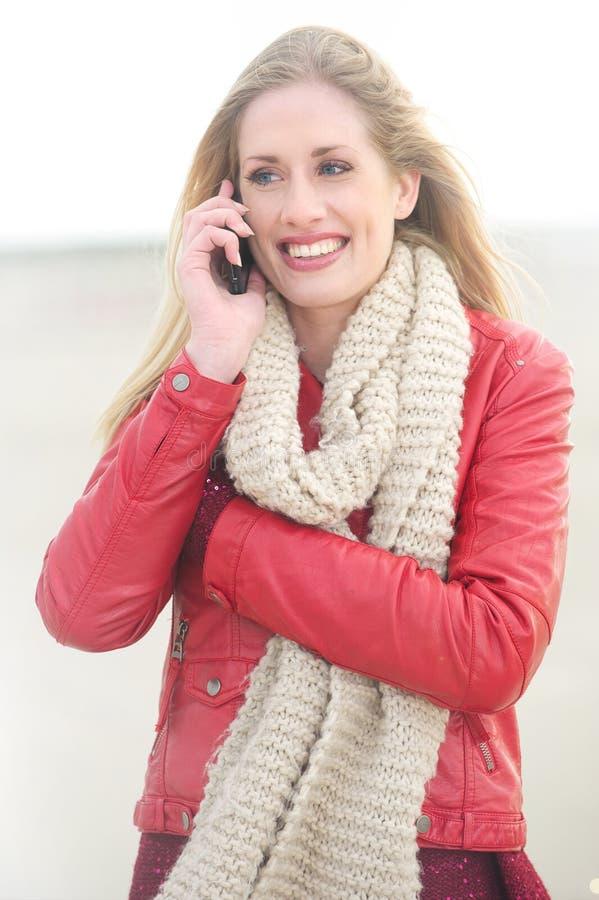 Portrait eines schönen blonden Mädchens mit Telefon stockfotografie